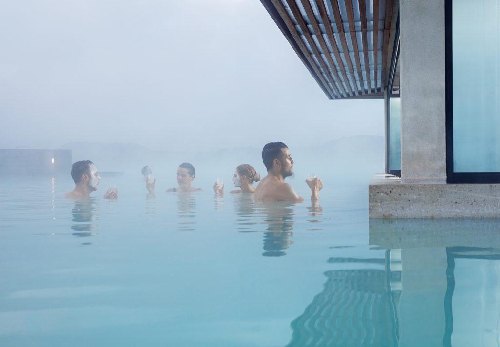 Badegäste mit Getränk im Wasser der Blauen Lagune