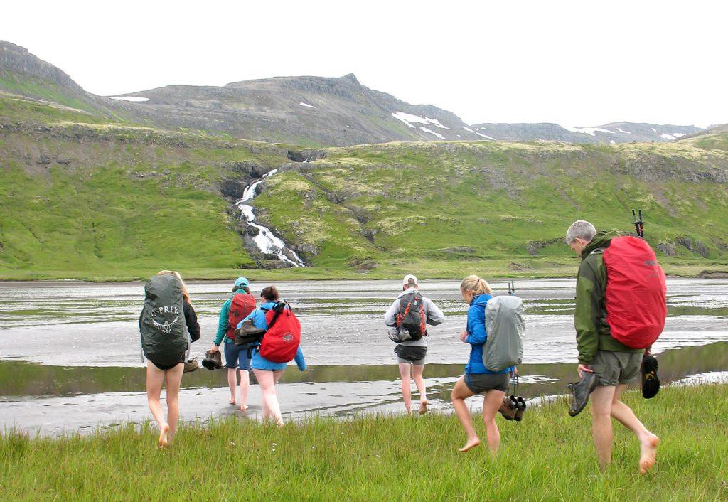 Reisegruppe in Island watet durch einen Fluss