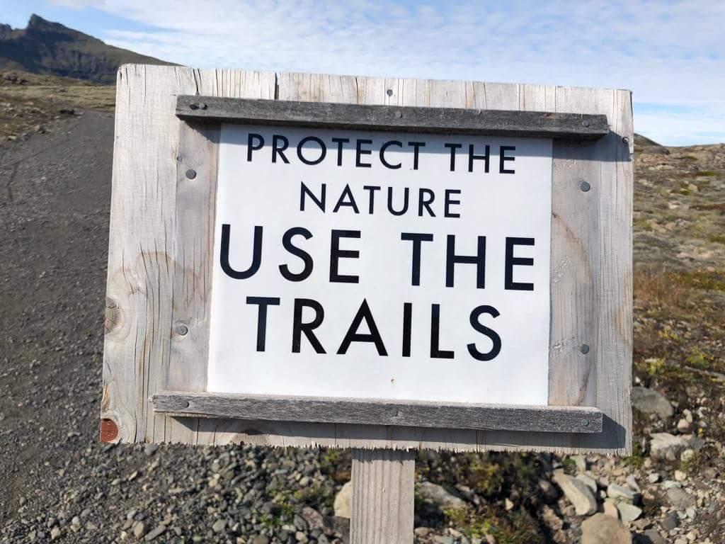 Schild in der Landschaft, Natur soll geschützt werden, auf dem Pfad bleiben.