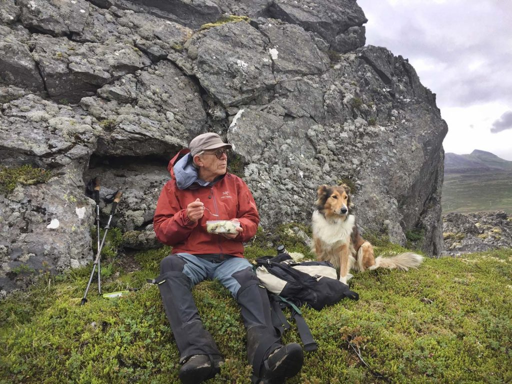 Vulkanologe Haraldur Sigurðsson auf Exkursion - Picknick mit Hund vor einem Felsen