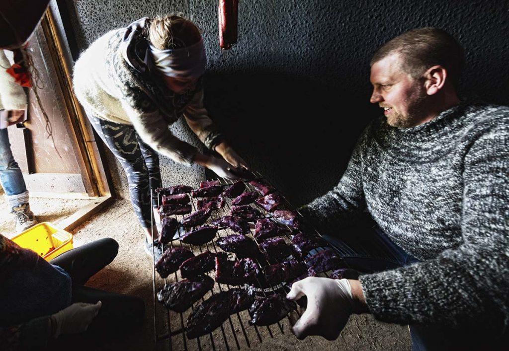 Europa, Island, Westisland, Hvalfjoerdur, Bauernhof Bjarteyjarsandur, Gudmundur, Rauecherhaus, mit Schafdung wird lammfleisch und Lammwuerste geraeuchert, Famlilie geht mit Gaesten Muscheln sammeln und bereitet sie hinterher gemeinsam zu